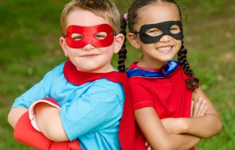 Pretty mixed race girl and Caucasian boy pretending to be superheroes