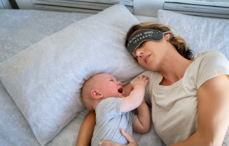 Tired mother with eye band trying to sleep while little toddler crying on bed.