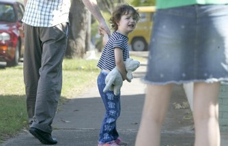 A crying child is led away by her father, 19 November 2003.