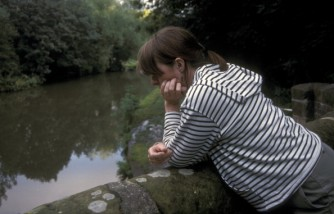 Woman looking depressed by canal UK