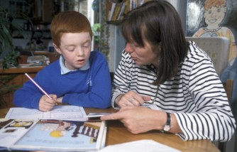 Mother helping her son with his homework, UK