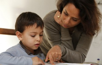 Mother helping a 6-year-old boy with his homework