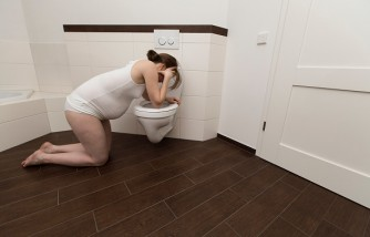 Young pregnant woman, 35 years old, feeling sick on a toilet.