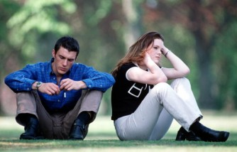 Stock Photography. A young couple in casual dress sitting in the park, the woman appears upset and has back turned on the man.
