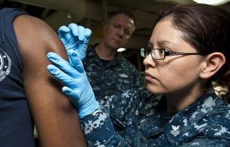 A sailor gives a smallpox shot.